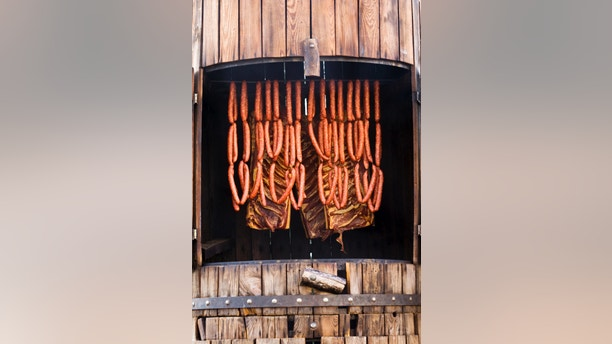 sausages and bacon being smoked in barrel-shaped smoker