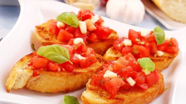 italian bruschetta with tomato,basil and cheese on purple plate