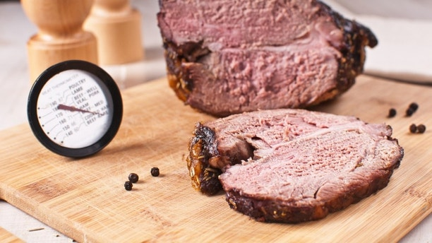 Roasted meat slice and thermometer for cooking