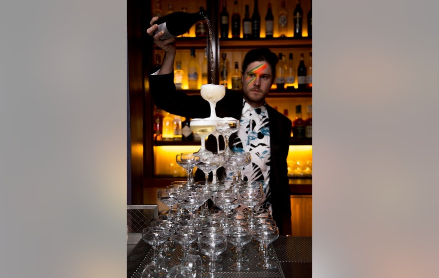 A face-painted bartender pours a champagne fountain.