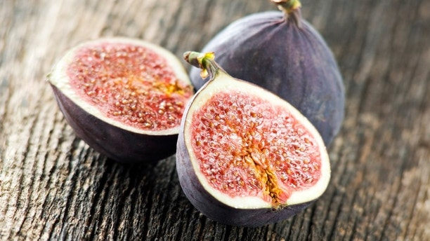 Fresh figs halved on wood close up shoot