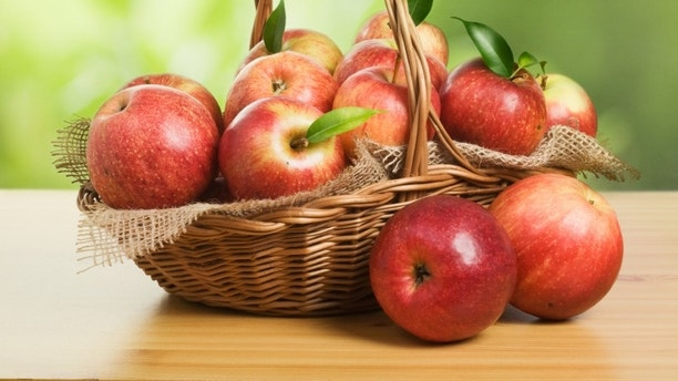 Jonagold apples in a basket on wooden table against garden background