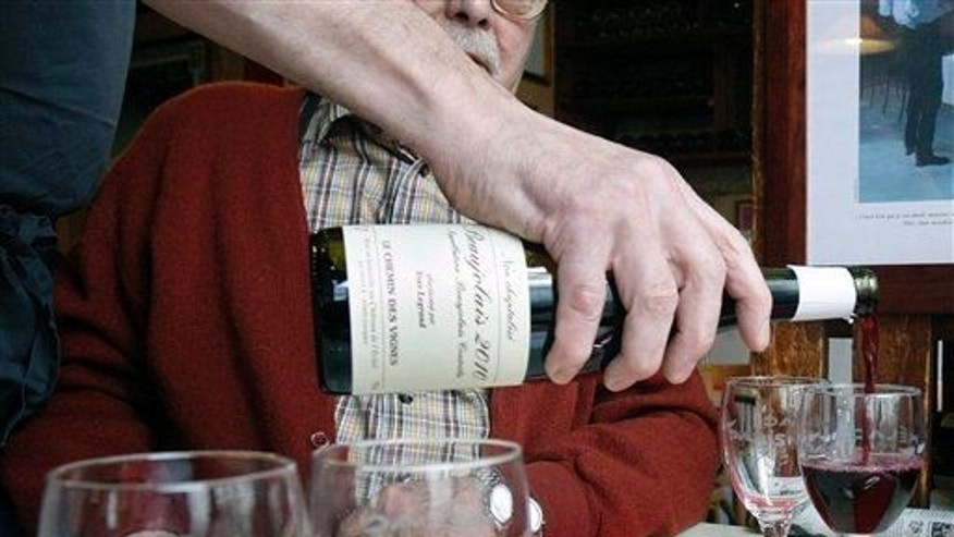 Restaurant owner Jacques Melac pours Beaujolais Nouveau wine in his customers' glasses in Paris, Nov. 18, 2010.