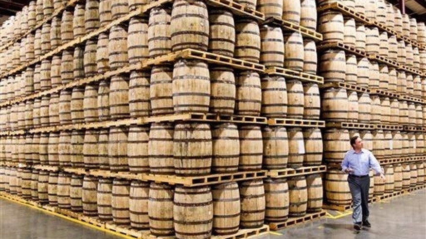 In this Aug. 14, 2014 file photo, a Diageo employee walks by barrels of whiskey stored in a new warehouse at the George Dickel distillery near Tullahoma, Tenn.