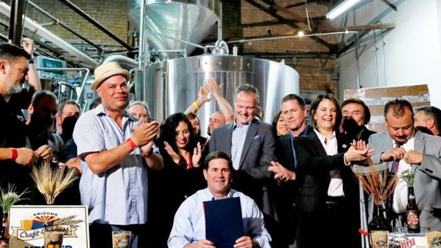 Supporters clap after Arizona Gov. Doug Ducey, center, signed Senate Bill 1030, Tuesday, March 31, 2015, at Four Peaks Brewery in Tempe, Ariz.