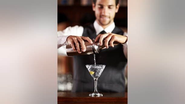 A handsome young bartender mixing a cocktail for a customer