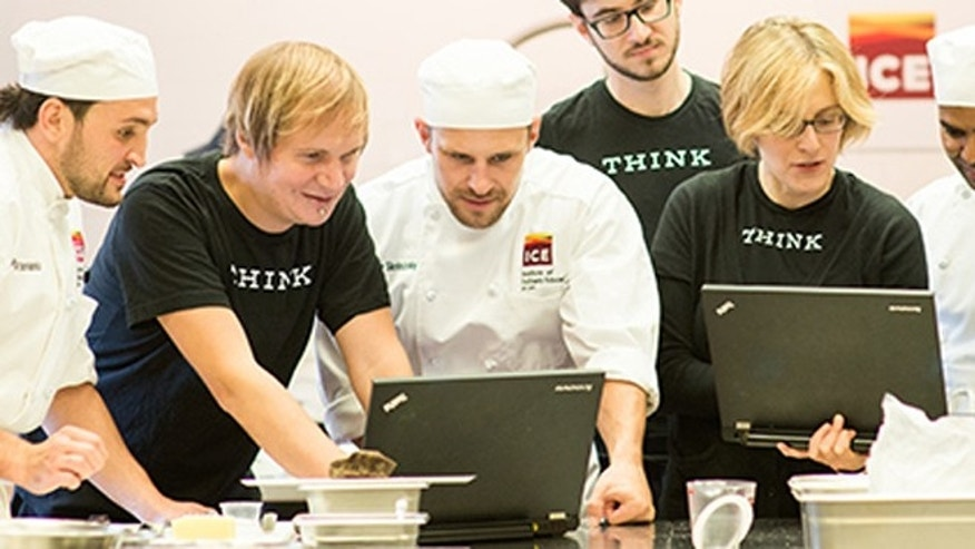 ICE chefs and IBM researchers hover over computers developing recipes.