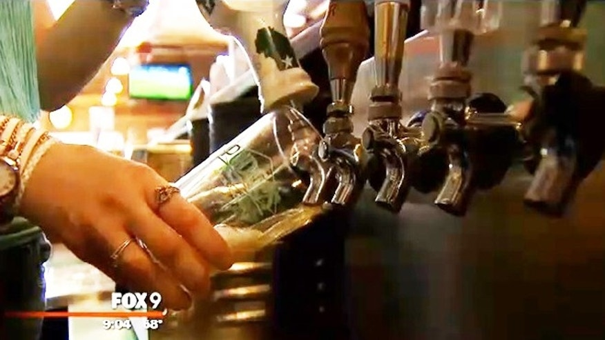 A server at Maple Tavern works the beer tap.