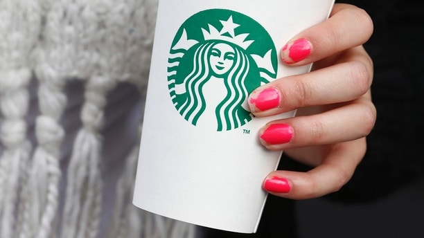 A woman holds a Starbucks takeaway cup in London October 24, 2012. Starbucks's reputation among consumers in Britain has been hit by wave of criticism of its tax affairs from politicians and the media, pollster YouGov said. REUTERS/Suzanne Plunkett (BRITAIN - Tags: BUSINESS FOOD) - RTR39IQG