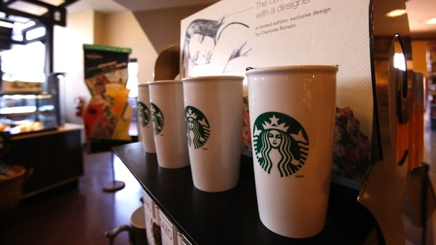 """Coffee mugs are pictured on display at a Starbucks coffee store in Pasadena, California July 25, 2013. Starbucks Corp on Thursday posted a bigger than expected jump in quarterly profit after new fruit """"Refresher"""" energy drinks and seasonal Frappuccino iced beverages helped drive more visits to shops in the United States, its top market.   REUTERS/Mario Anzuoni  (UNITED STATES - Tags: BUSINESS FOOD) - RTX11ZCQ"""