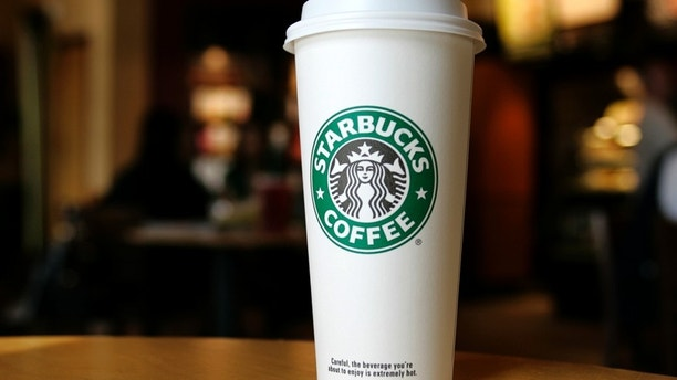 A cup displaying the Starbucks Coffee logo is pictured at one of the coffee chain's store in Boca Raton, Florida January 19, 2010. REUTERS/Joe Skipper (UNITED STATES - Tags: BUSINESS FOOD) - RTR292ZA