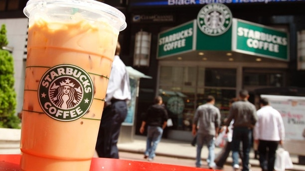 A Starbucks drink is seen on a table in New York's Times Square April 21, 2010. Shares in coffee chain Starbucks, which is due to report results later in the day, fell 0.6 percent. McDonald's encroached further into Starbucks Corp territory this quarter by introducing lower-priced frappes designed to compete with Frappuccinos. REUTERS/Shannon Stapleton (UNITED STATES - Tags: BUSINESS) - RTR2D3CV