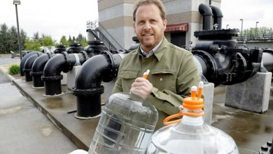 Clean Water Services spokesperson Mark Jockers shows sealed containers of highly purified water from their facility in Forest Grove, Ore.