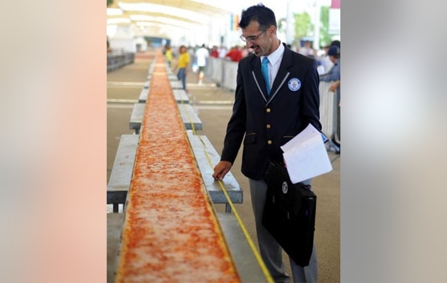 More than 60 of Italy's best pizza-makers worked through the night to create a 5234 ft., or nearly a mile long pizza at Milan's world fair.