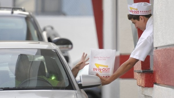 In this June 11, 2010 photo, a customer reaches for his order from the drive-through at In-N-Out Burger in the Hollywood area of Los Angeles. Amid complaints of obesity and lines of idled cars stretching into neighborhood streets, this blue-collar town is banning new drive-throughs in hopes of shedding its reputation as a haven for convenient, fatty foods. (AP Photo/Adam Lau)