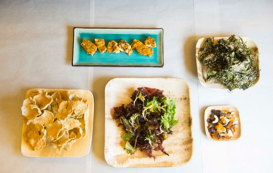 An array of dulse-infused snacks being tested by the Food Innovation Center including crispy rice crackers, smoked dulse popcorn peanut brittle, and salad topped with dulse dressing.