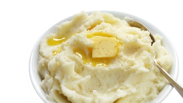 Bowl of mashed potato with melting butter and a sprinkle of nutmeg.