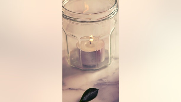 Vintage feel camellia flower and jar candle on marble