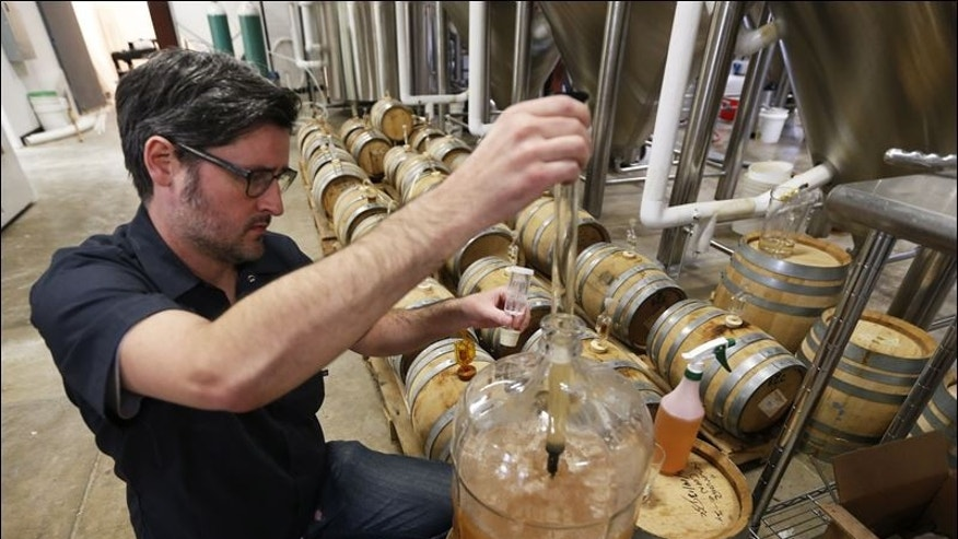 Kevin O'Leary, co-owner of Ardent Craft Ales, takes a sample of Persimmon beer at his brewing facility in Richmond, VA.