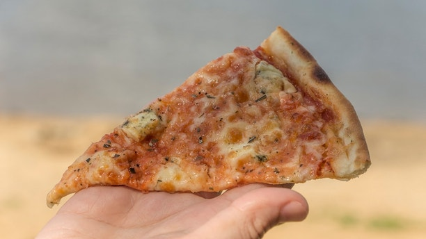 Fast food, female hand holding a slice of pizza, on the beach.