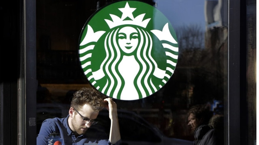 FILE - In this Jan. 11, 2016, photo, a man sits inside a Starbucks, in New York. (AP Photo/Mark Lennihan)