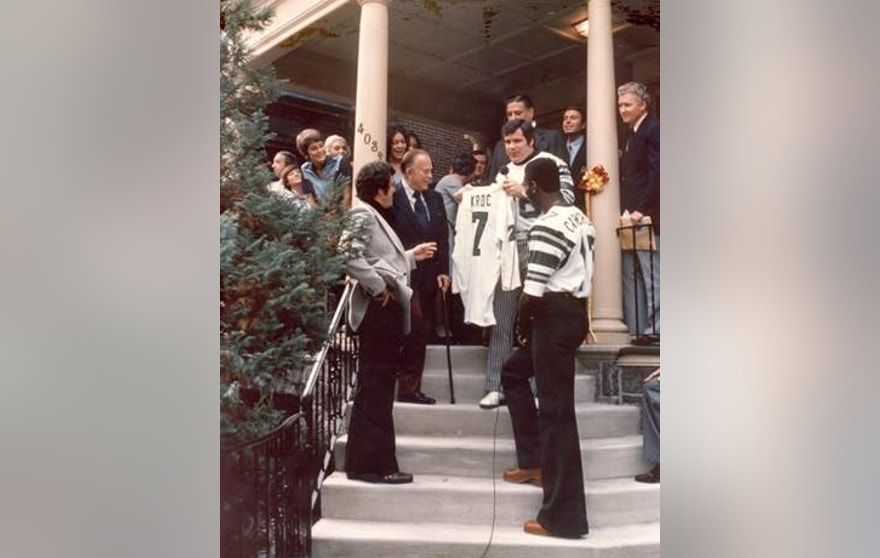 Philadelphia Eagles Players present jersey to Ray Kroc at the first Ronald McDonald House, 1974. A week-long Shamrock Shake promotion funded the purchase of the four-story, seven-bedroom house which allowed families to stay close to their kids being treated in the hospital nearby.