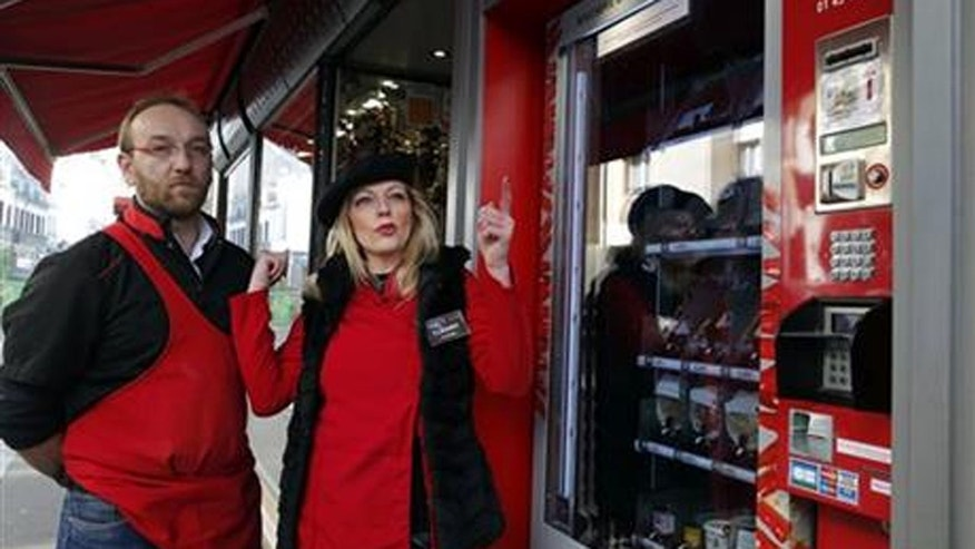 Tuesday, March 15, 2016: Florence, right, and Michel Pouzol pose by the first meat vending machine installed in the French capital, in Paris.