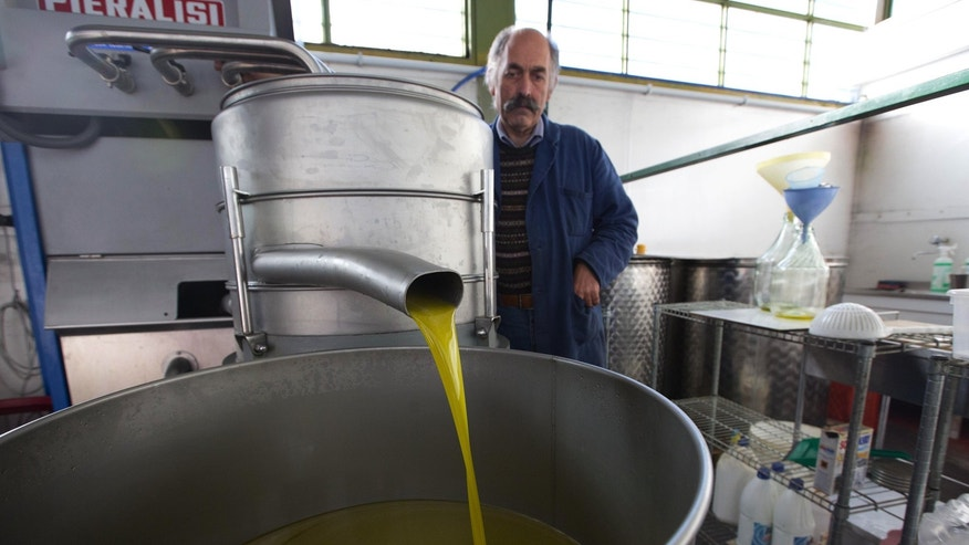 Italian olive oil producer Augusto Spagnoli inspects his production line in this 2014 file photo.
