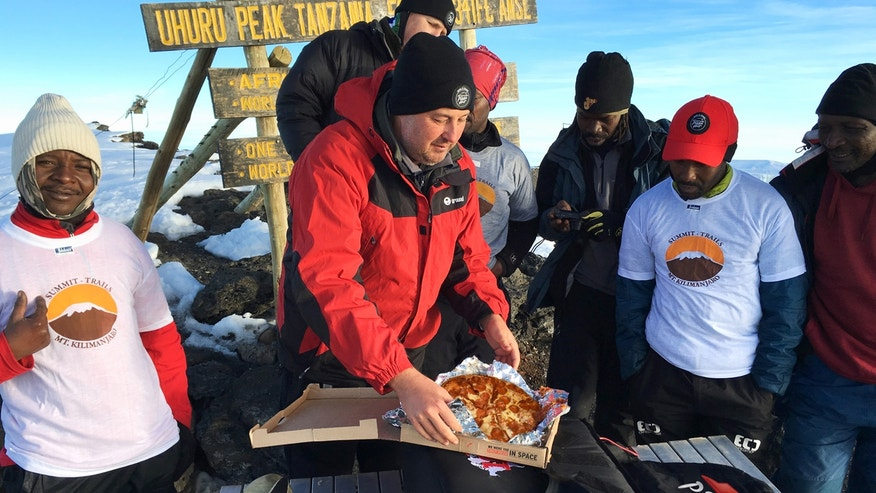 General Manager of Pizza Hut Africa, Randall Blackford, enjoys some pepperoni pizza with a team of Pizza Hut employees at the summit of Mt. Kilimanjaro on May 9.