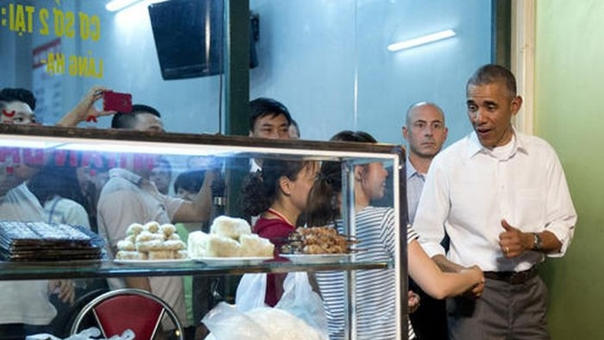 President Barack Obama greets women at the door as he walks from the Bún ch? Huong Liên restaurant after having dinner with American Chef Anthony Bourdain in Hanoi, Vietnam, Monday, May 23, 2016.