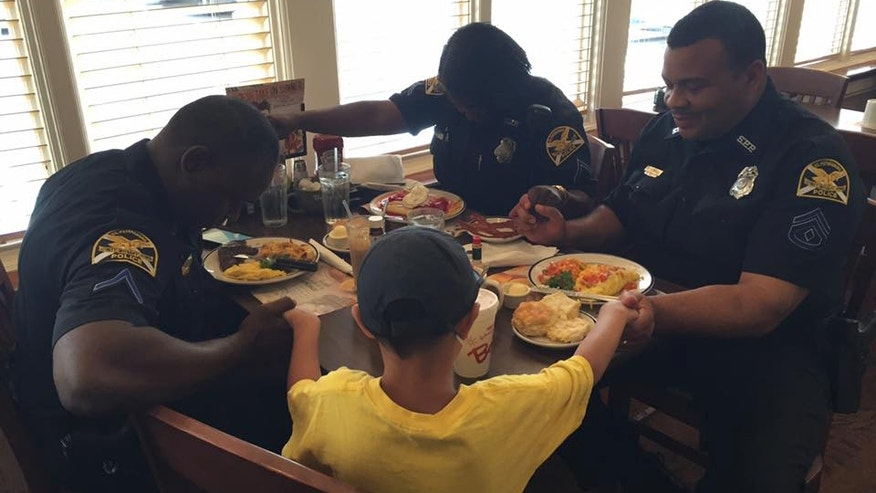 Cops at a St. Petersburg, Fla. Bob Evans bow their heads in prayer with a 6-year-old diner.