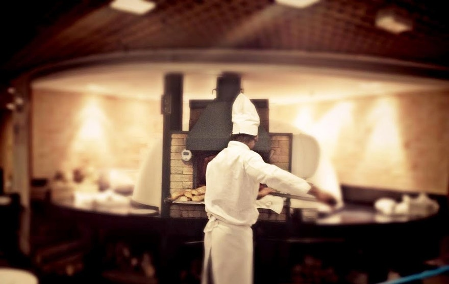 A chef at Ráscal, a popular Italian restaurant chain in Brazil, tends to pizza in a wood-fired oven.  There are over 8,000 pizza parlors that produce close to a million pizzas a day in São Paulo, Brazil.