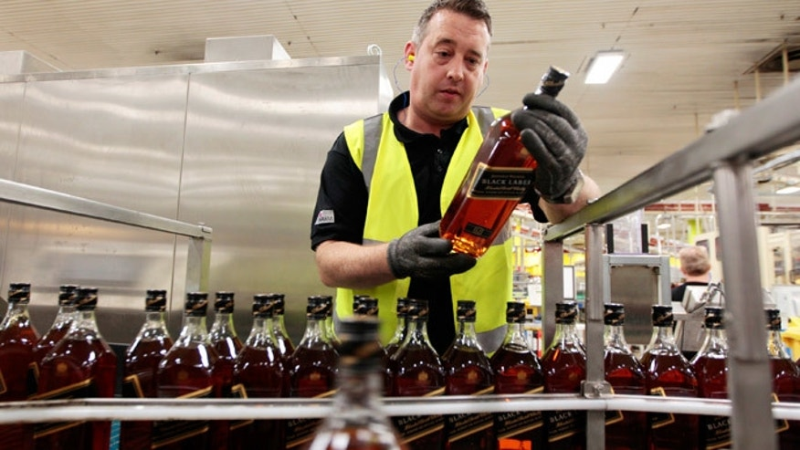 A worker inspects a bottle of Johnnie Walker whisky at the Diageo-owned Shieldhall bottling plant in Glasgow, Scotland.