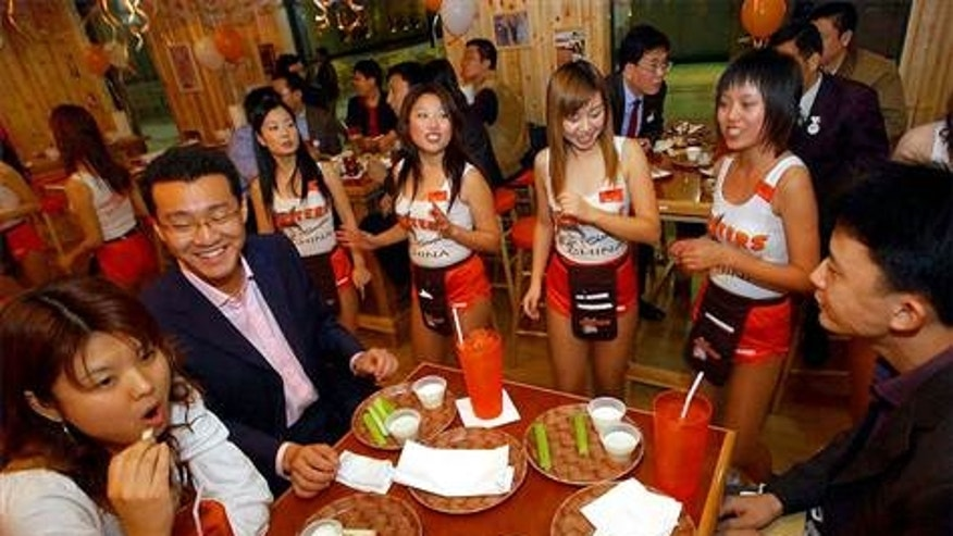 Chinese waitresses dance the Hokey-Pokey Friday in front of guests during the pre-opening of Hooters in Shanghai, China. The first Hooters restaurant in Asia opening in Shanghai in 2004.