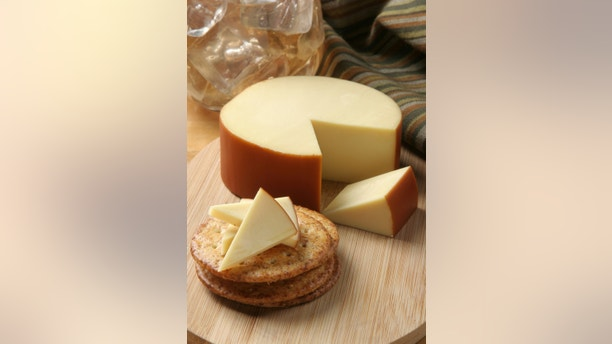 a wheel of smoked gouda cheese served with crackers