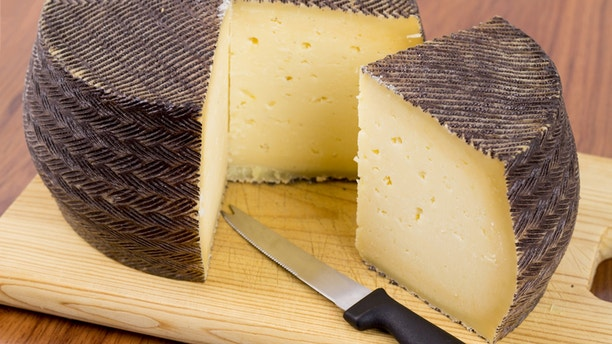 Spanish manchego cheese portion with a special cutting knife on a wooden board
