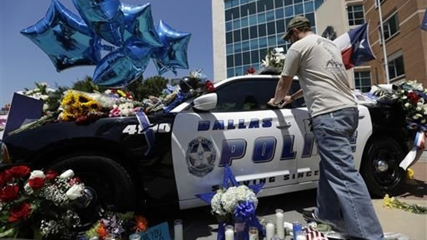 Michael O'Mahoney, a former police officer, places his patch on a make-shift memorial outside the Dallas police headquarters.