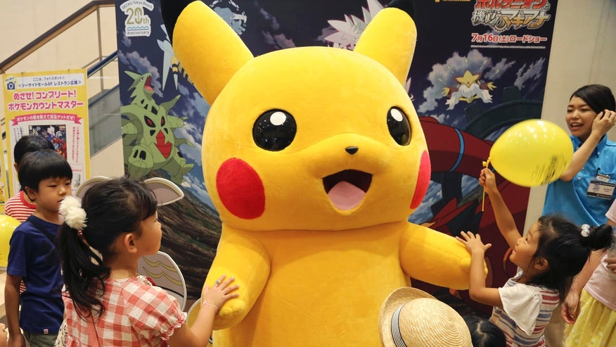 In this Monday, July 18, 2016 photo, a stuffed toy of Pikachu, a Pokemon character, is surrounded by children during a Pokemon festival in Tokyo, Japan.