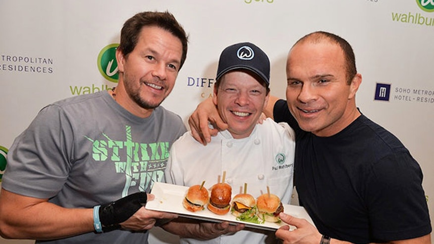 Mark Wahlberg,  Wahlburgers executive chef Paul Wahlberg with former Toronto Maple Leaf Tie Domi showcase some of the chain's burgers.