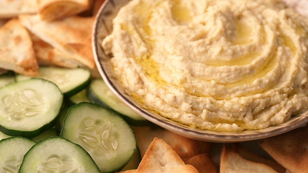 High-resolution, full-frame, close-up digital capture of a bowl of freshly made hummus with sliced Arabian cucumbers and golden toasted pita points. Surface of hummus is drizzled with extra virgin olive oil.