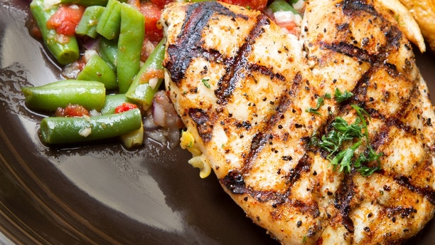 Healthy grilled chicken on a plate with fresh cut french fried potatoes and green beansq.  Chicken breast is garnished with parsley