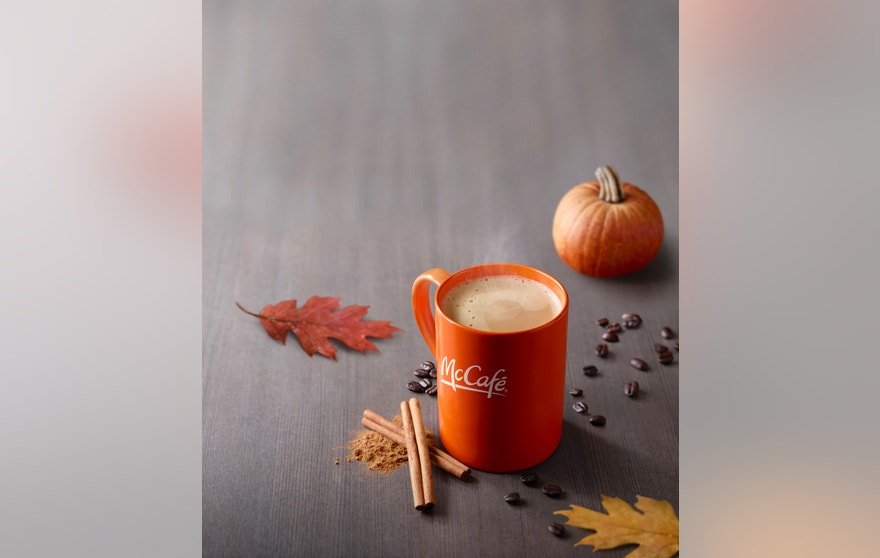 Pumpkin Spice Latte; in McCafe branded orange mug with imaged steam - cinnamon sticks, coffee beans, autumn leaves and miniature pumpkin in variable focus around mug - dark, wood table surface in receding focus
