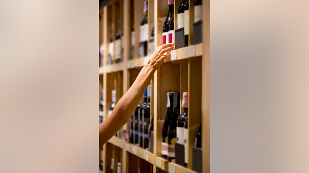 Human hand is buying bottle of wine, selective focus