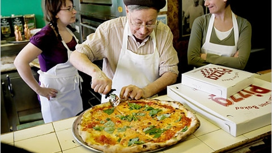 Di Fara pizzeria owner Dominico DeMarco slices one of his legendary pies.