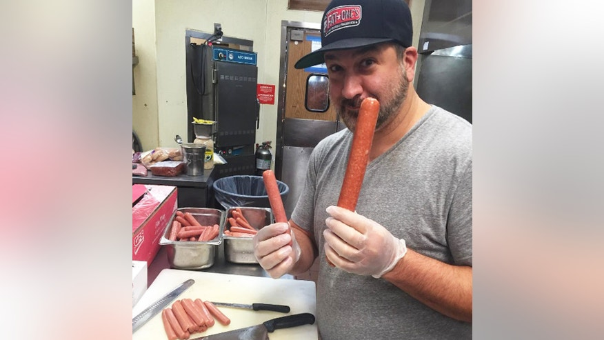 "Joey Fatone compares his extra-large ""Fat One"" hot dog to a smaller signature sausage. The former boy band member is opening a gourmet hot dog kiosk in Orlando Sept. 10."