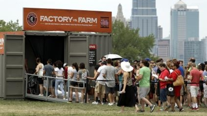 People line up to view a display contrasting processed versus fresh food production at Chipotle's Cultivate Festival in Kansas City, Mo. in July.
