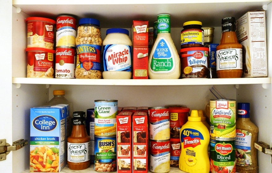 West Palm Beach, USA - October 9, 2015: Image of two kitchen pantry shelves filled with groceries. Included among the groceries are canned soups, tomatoes, beans and corn, salad dressings, barbecue sauce, peanuts, mustard, cake mixes, chicken broth, and a variety of other cooking and baking ingredients. Many popular brand names are represented, such as Campbells, Green Giant, Del Monte, Bush's, Miracle Whip, Betty Crocker, Libbys, Duncan Hines and Kraft