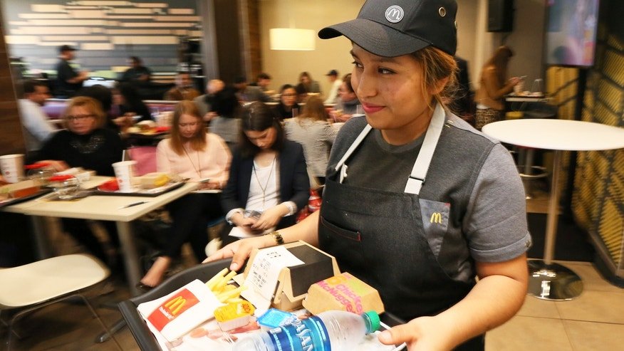 A McDonald's employee delivers a meal as part of the new table service feature at select restaurants.