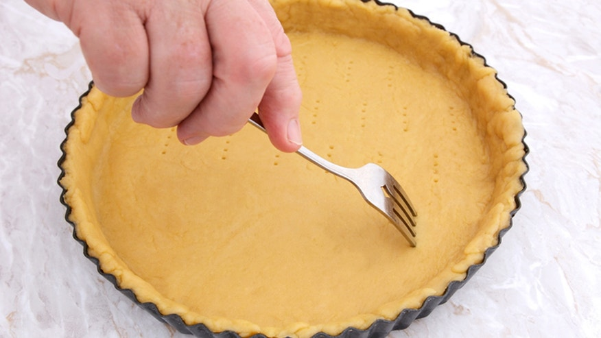 Woman uses metal fork to prick ventilation holes in an uncooked pie crust