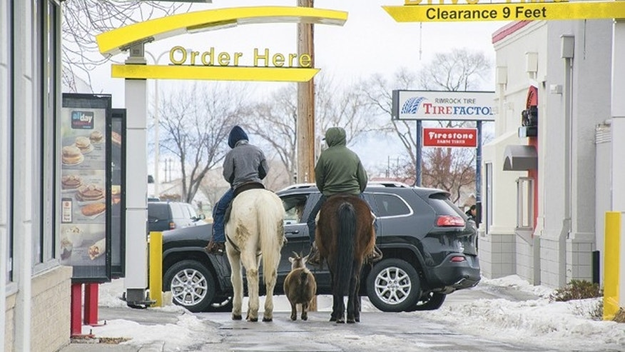 In this photo taken Dec. 30, 2016, Trajen Collins, left, is joined by Joel Perez as they ride their horses through the McDonald's drive-thru with a pet goat in tow in Powell, Wyo.